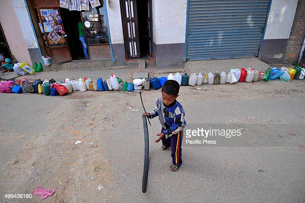 Nepalese kid plays while waiting for his parents' time to buy kerosene For the past few months neighboring India has blocked the transportation of...
