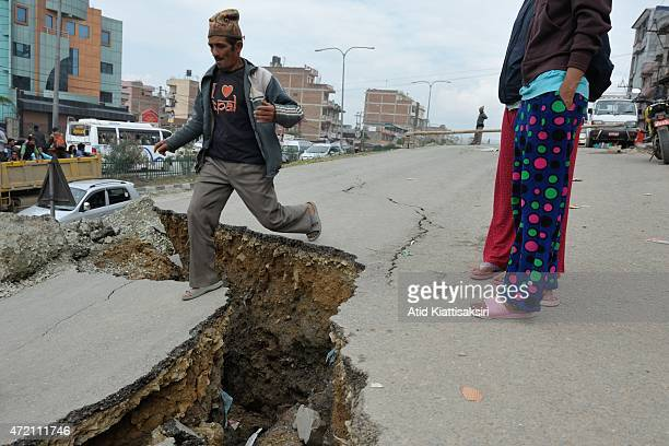 Nepalese man jumps across a cracked road after the earthquake hit Nepal