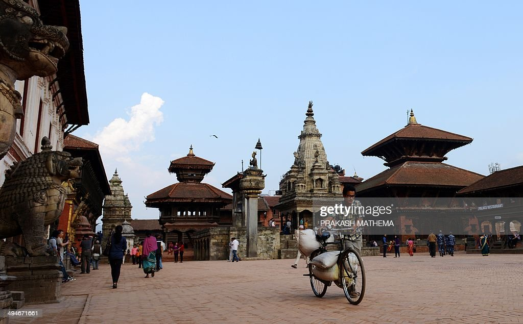 A Nepalese man pushes his bicycle as he passes through Bhaktapur Durbar Square in Bhaktapur some 12 kilometers southeast of Kathmandu on May 30 2014...