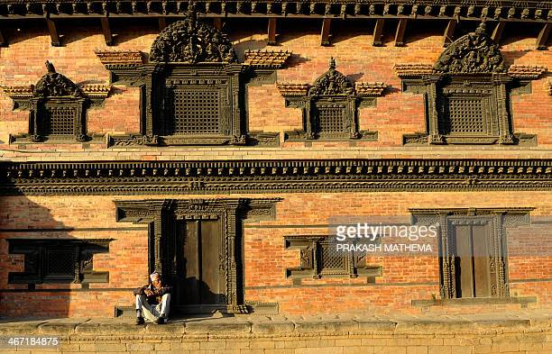 A Nepalese man sits beside intricately carved windows and doors at the Bhaktapur Durbar Square area in Bhaktapur some 12 kilometres southeast of...