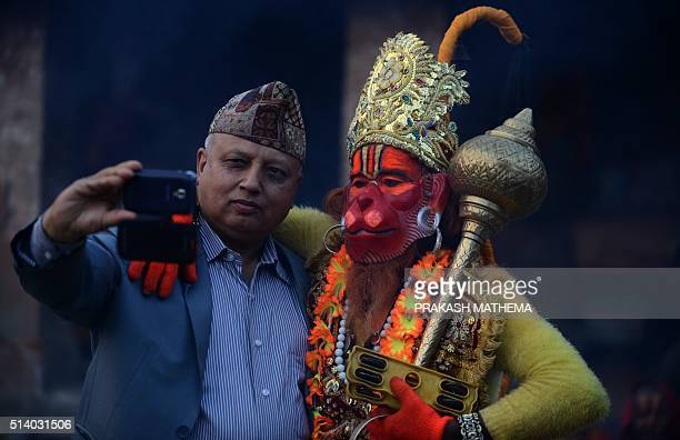 A Nepalese man takes a selfie with a Sadhu dressed as Hanuman the Monkey God in the Hindu Pantheon at the Pashupatinath temple on the eve of the...