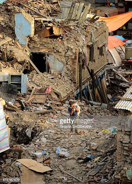 A Nepalese man walks past damaged houses following an earthquake in Kathmandu on May 26 2015 The April 25 disaster was followed by another massive...