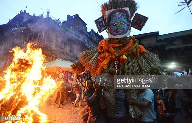 Nepalese men carry a straw effigy of Ghanta Karna to be set alight during celebrations of the Hindu festival of 'Gathemangal' also known as Ghanta...