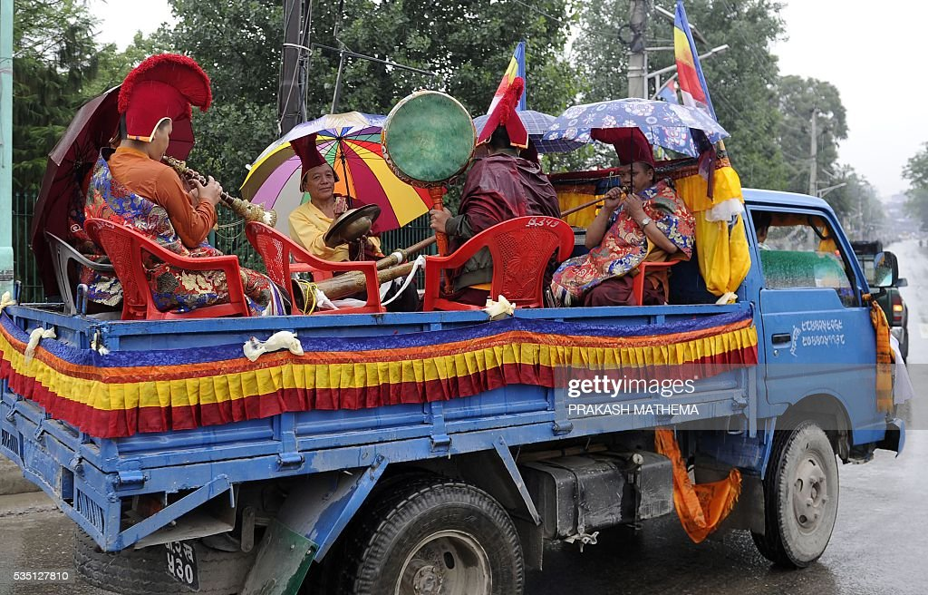 Nepalese monks playing instruments on a truck take part in a procession to mark the 9th International Everest Day in Kathmandu on May 29, 2016. Nepal marks May 29 as International Mount Everest (Sagarmatha) Day, in memory of its first successful ascent on May 29, 1953 by Edmund Hilary and Tenzing Norgay. / AFP / PRAKASH