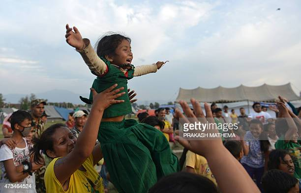 A Nepalese mother and child participate in a 'laughter yoga' session to help relieve trauma among survivors of two earthquakes which struck the...