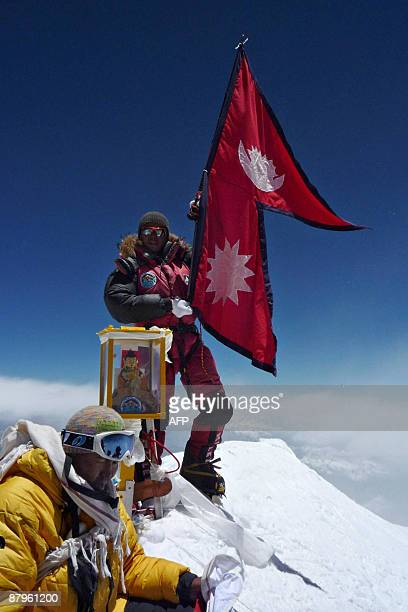 Nepalese mountaineer Pemba Dorje Sherpa who currently holds the record for the fastest ascent of Everest at eight hours and 10 minutes unfurls a...