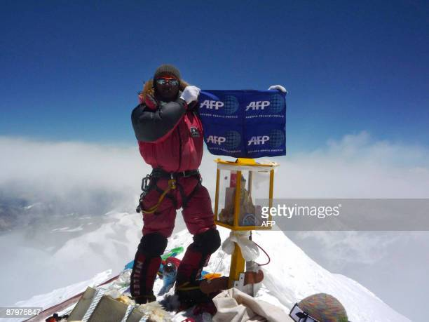 Nepalese mountaineer Pemba Dorje Sherpa who currently holds the record for the fastest ascent of Everest at eight hours and 10 minutes unfurls a flag...