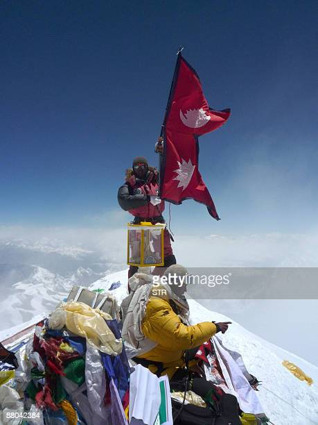 Nepalese mountaineer Pemba Dorje Sherpa who currently holds the record for the fastest asscent of Everest at eight hours and 10 minutes unfurls a...
