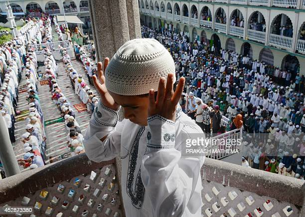 A Nepalese Muslim child offers Eid prayers on the first day of the Edi alFitr festival at Kashmiri Mosque in Kathmandu on July 29 2014 Muslims around...