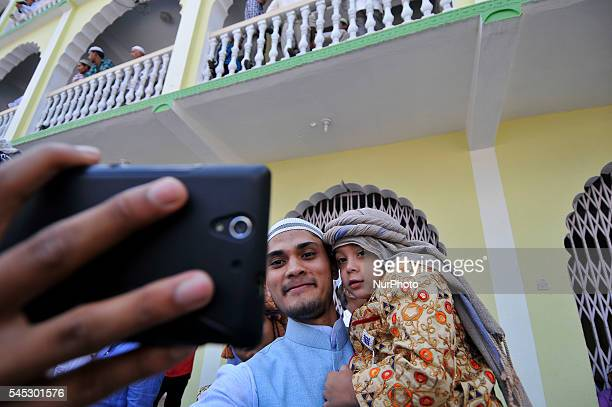 A Nepalese Muslim takes pictures during celebration of Eid alFitr on July 7 2016 in Kashmire Jame Mosques Kathmandu Nepal by attending special...