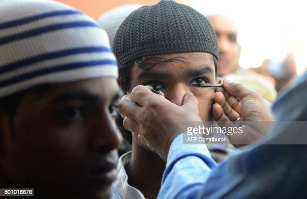 Nepalese Muslims apply traditional Kohl eyeliner before offering Eid prayers at the start of the Eid alFitr holiday marking the end of Ramadan at the...