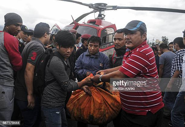 Nepalese officials carry the remains of those killed in a helicopter crash into the morgue of a Teaching Hospital in Kathmandu on August 8 2016 A...