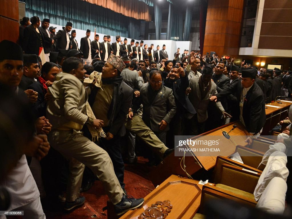 Nepalese opposition lawmakers turn desks over as they obstruct the meeting of Nepal's constituent assembly ahead of the midnight deadline to agree on...