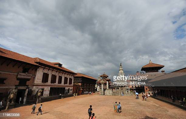 Nepalese pedestrians pass through Bhaktapur Durbar Square in Bhaktapur some 12 kilometers southeast of Kathmandu on July 21 2011 Bhaktapur a UNESCO...