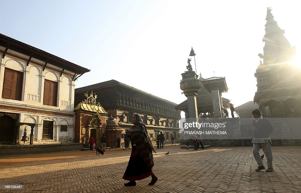 Nepalese pedestrians pass through the Bhaktapur Durbar Square in Bhakatpur some of 12 kilometers southeast of Kathmandu on February 18 2011 Bhaktapur...