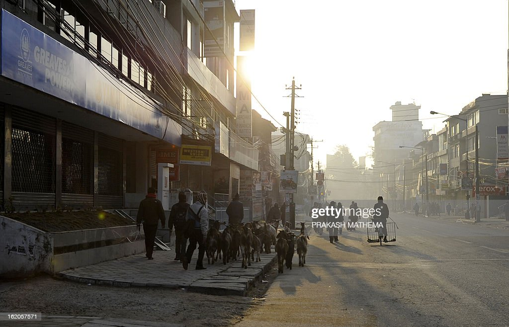 Nepalese pedestrians walk on the main market street during a general strike called by the Communist Party of Nepal-Maoist in Kathmandu on February 19, 2013.The nationwide strike was organised by a hardline breakaway faction of the country's ruling Maoists in protest over an attempt by the mainstream political parties to form a unity government led by the Supreme Court's chief justice. AFP PHOTO/Prakash MATHEMA