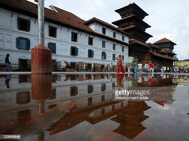 Nepalese pedestrians walk past an ancient royal palace at Durbar square in Kathmandu on August 12 2011 The Durbar Square which holds the palaces of...