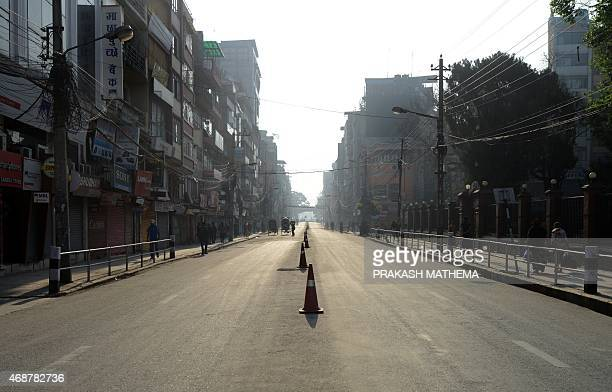 Nepalese pedestrians walk past closed shops in the main market area during a three day nationwide strike led by the Unified Communist Party of Nepal...