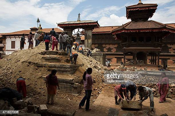 Nepalese people clear rubble from a collapsed pagoda in Durbar Square in Bhaktapur Nepal on April 30 2015 On April 25 Nepal suffered a magnitude 78...