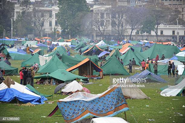 Nepalese people gather near temporary shelters set up in open areas of an Army ground in Kathmandu on April 27 two days after a 78 magnitude...