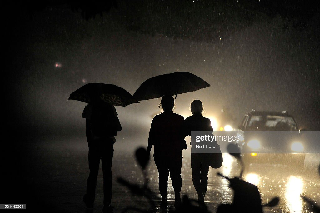 Nepalese people shelters under an umbrella as approaching towards their home during heavy rainfall on May 26, 2016.