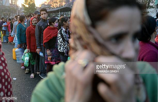 Nepalese people stand in line for water at a camp set up in the wake of a devastating earthquake in Kathmandu on April 28 2015 Hungry and desperate...
