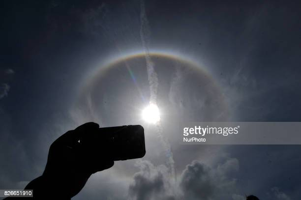 Nepalese people taking photos using mobile photos as a 22° halo surrounded the sun as it shined on Kathmandu Nepal on Saturday August 5 2017 The...