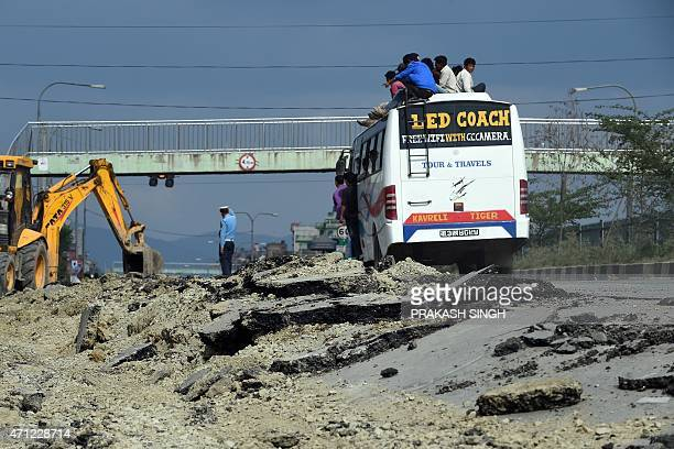 Nepalese people travel on the roof of a bus as they drive past a damaged road on the outskirts of Kathmandu on April 26 2015 International aid groups...