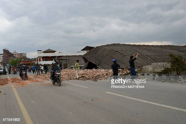 Nepalese people walk past a collapsed building of the Nepalese Army in Kathmandu on April 25 2015 A powerful 79 magnitude earthquake struck Nepal...