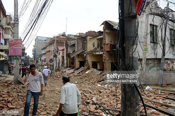 Nepalese people walk past collapsed buildings at Lalitpur on the outskirts of Kathmandu on April 25 2015 A powerful 79 magnitude earthquake struck...