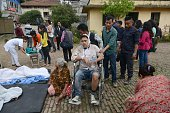 Nepalese people wheel an injured man into an open area following an 79 earthquake at Lalitpur on the outskirts of Kathmandu on April 25 2015 A...