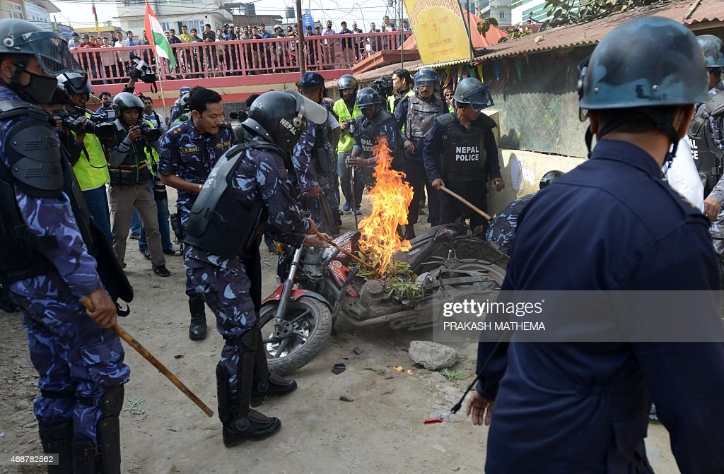 Nepalese Police Extinguish A Burning Motor Bike Which Was