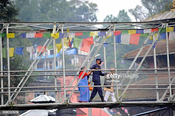 A Nepalese police officer helps elder people to cross extension bridge for religious puja during the celebration of Kuse Aunsi or Father's Day at...
