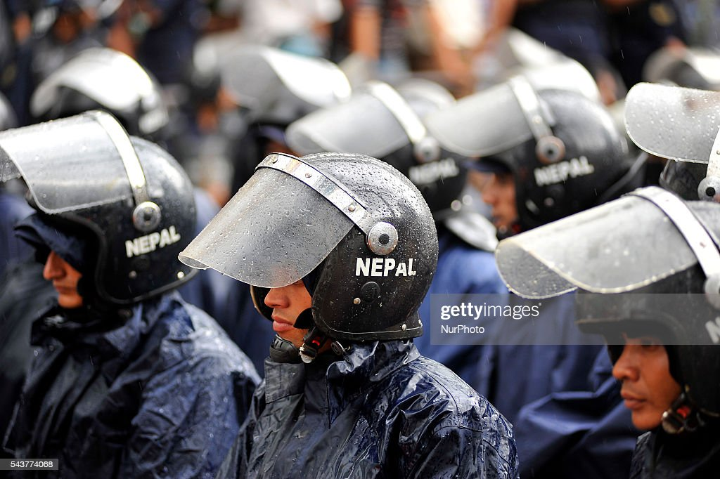 Nepalese police personnel guard on on sudden rainfall during a protest rally to pressurize Government of Nepal for Black marketing, corruption, Price Hiking, Smuggling and remedy leave of Cadres & Political Leader of CPN Maoist at Singha Durbar, Kathmandu, Nepal on June 30, 2016.