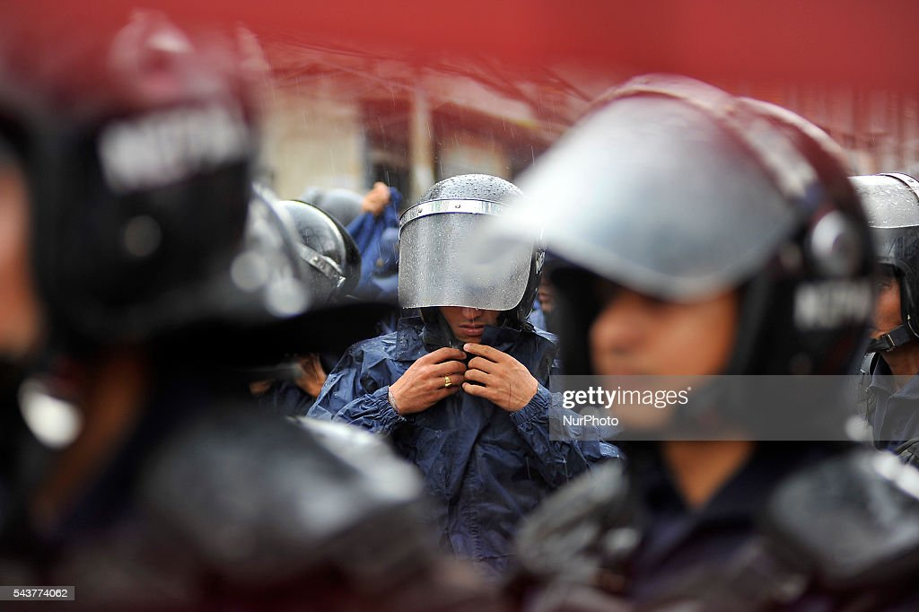 Nepalese police personnel wearing raincoat as sudden rainfall during a protest rally to pressurize Government of Nepal for Black marketing, corruption, Price Hiking, Smuggling and remedy leave of Cadres & Political Leader of CPN Maoist at Singha Durbar, Kathmandu, Nepal on June 30, 2016.