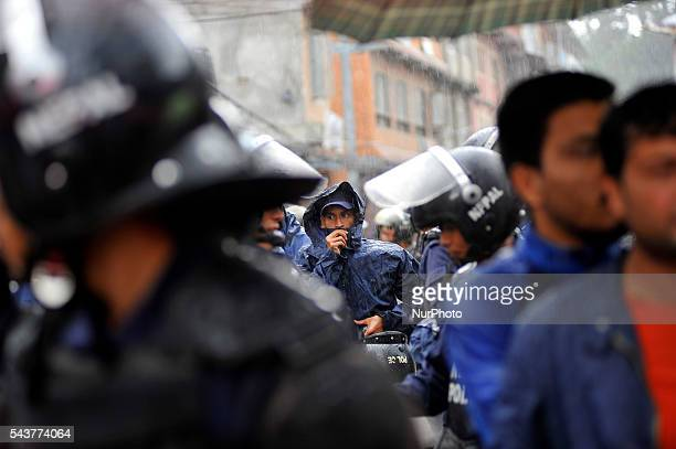 Nepalese police personnel wearing raincoat as sudden rainfall during a protest rally to pressurize Government of Nepal for Black marketing corruption...