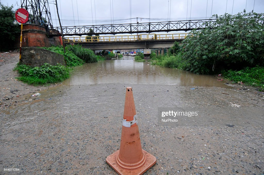 Nepalese police puts warning attend in front of Water logged at Sanepa Kalo Pul, after vehicle stuck at Kathmandu on July 1, 2016. Due to the poor water drainage management system, yearly water logged problem seen at Sanepa, which affecting more than 3 millions of Motors and motorbikes.