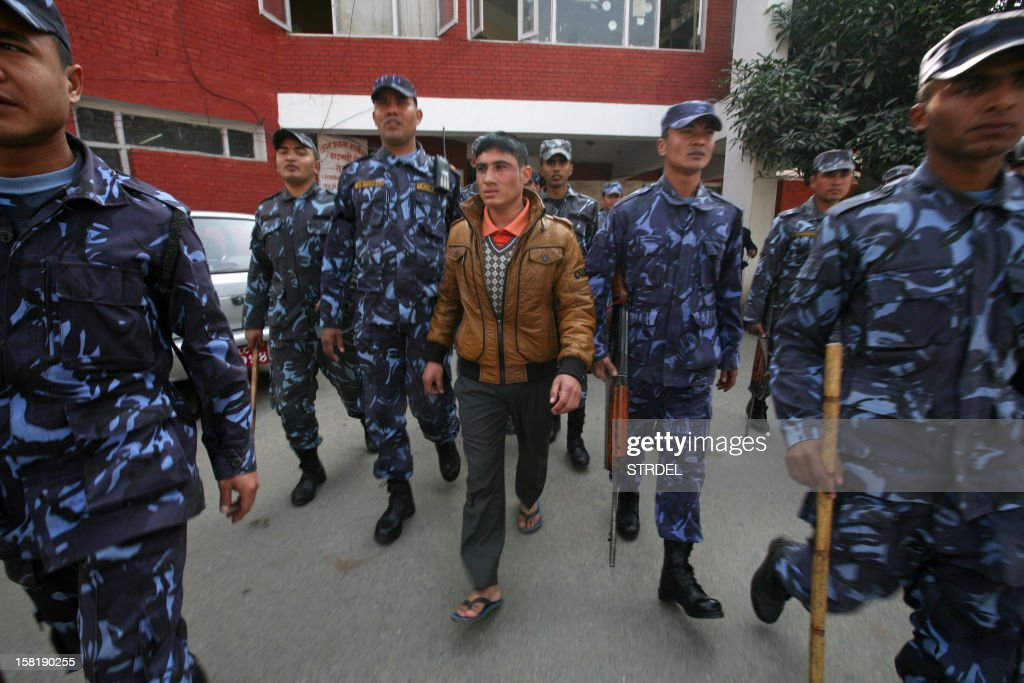 Nepalese police walk with 25-year old Padam Kunwar, who was arrested for slapping Unified Communist Party of Nepal (Maoist) Chairman Pushpa Kamal Dahal, in Kathmandu on November 11, 2012. The leader of Nepal's ruling Maoists put up the bail money December 11 to free an inmate in prison awaiting trial for slapping the former revolutionary in the face, the party said.