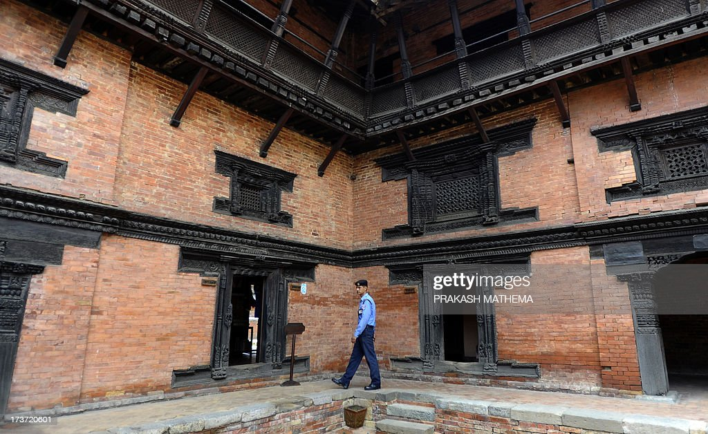 A Nepalese policeman walks at the Durbar Square in Lalitpur on July 17, 2013. Lalitpur's Durbar Square, a UNESCO World Heritage Site, is best known for its rich cultural heritage, particularly its tradition of arts and crafts. AFP PHOTO/ Prakash MATHEMA