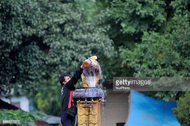 A Nepalese priest offering milk towards Nag or Sanke God during Nag Panchami or Snake Day Festival celebrated at Naxal Kathmandu Nepal on August 7...