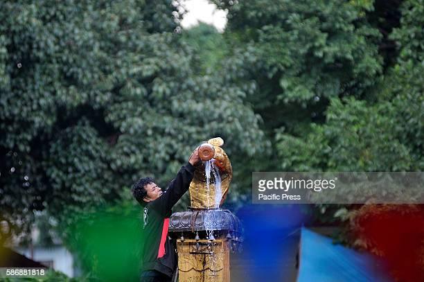 Nepalese priest offering milk towards Nag or Sanke God during Nag Panchami or Snake Day Festival celebrated at Naxal Kathmandu Nag Panchami is the...