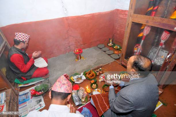 Nepalese Priests offering rituals before spreading barley seeds to grow as 'Jamara' a religious holy flower as the offering of Goddess Durga during...