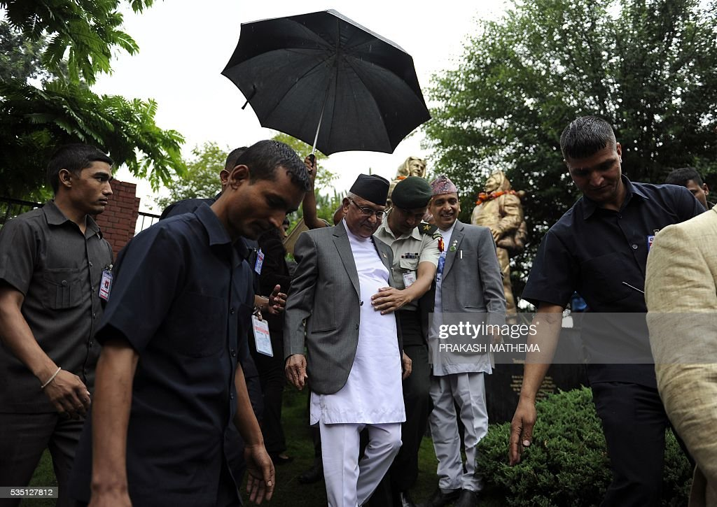 Nepalese Prime Minister KP Oli Sharma (C) returns after offering garlands to the statues of Tenzing Norgay and Edmund Hillary to mark 9th International Everest Day in Kathmandu on May 29, 2016. Nepal marks May 29 as International Mount Everest (Sagarmatha) Day, in memory of its first successful ascent on May 29, 1953 by Edmund Hilary and Tenzing Norgay. / AFP / PRAKASH