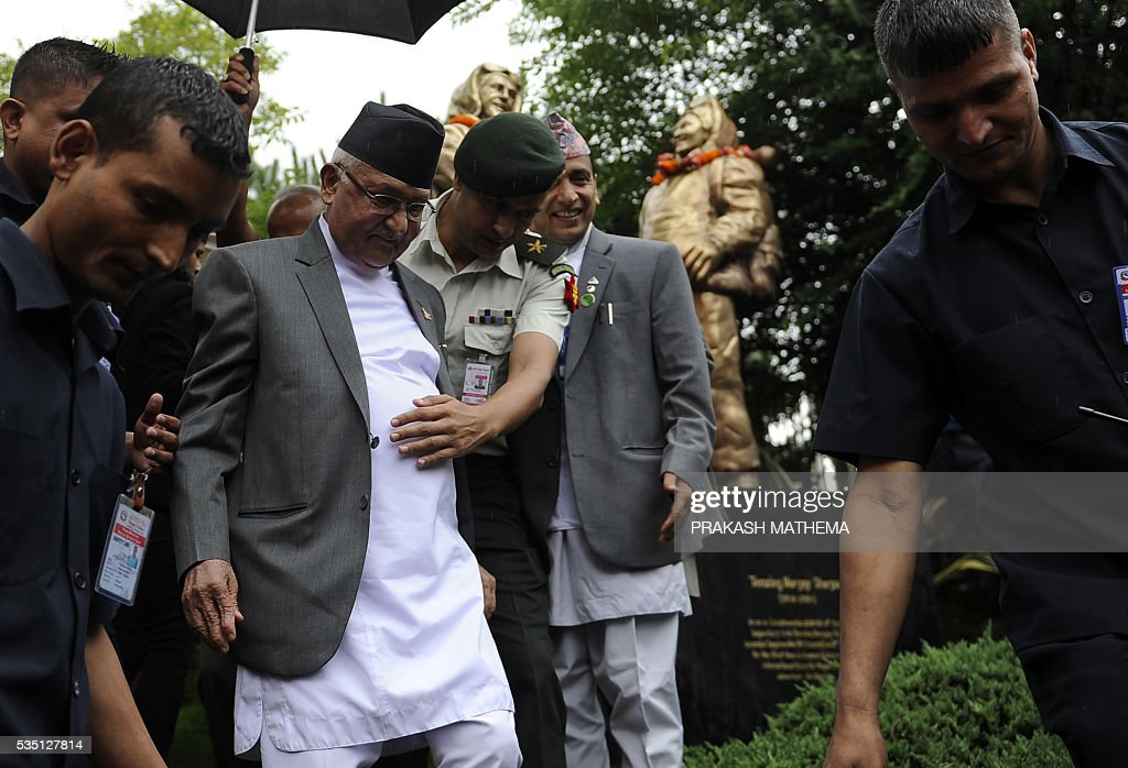 Nepalese Prime Minister KP Oli Sharma (2nd L) returns after offering garlands to the statues of Tenzing Norgay and Edmund Hillary to mark 9th International Everest Day in Kathmandu on May 29, 2016. Nepal marks May 29 as International Mount Everest (Sagarmatha) Day, in memory of its first successful ascent on May 29, 1953 by Edmund Hilary and Tenzing Norgay. / AFP / PRAKASH