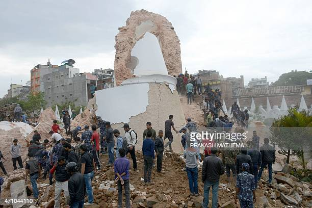 Nepalese rescue members and onlookers gather at the collapsed Dharahara Tower in Kathmandu on April 25 2015 A powerful 79 magnitude earthquake struck...