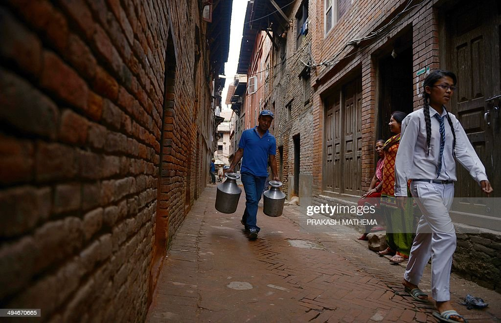 A Nepalese resident carries containers after collecting water from a tanker in Bhaktapur, some 12 kilometers south-east of Kathmandu on May on 30, 2014. Residents in the Kathmandu Valley routinely suffer from a shortage of drinking water, and the government water department says that it has managed to supply only one fourth of the total water demand in the city. AFP PHOTO/Prakash MATHEMA