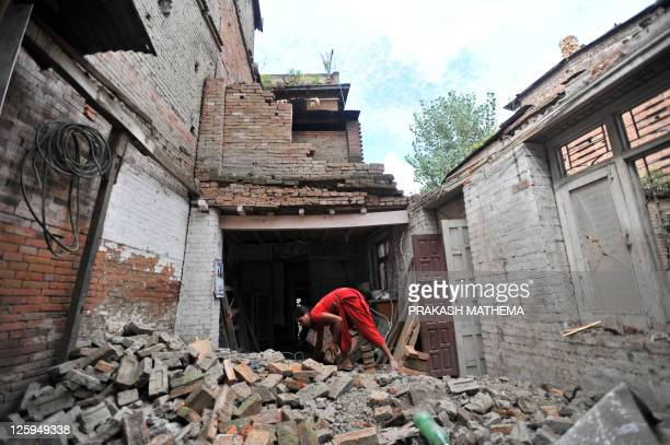 A Nepalese resident clears rubble from collapsed and damaged houses following an earthquake at Bhaktapur some 12 kilometres southeast of Kathmandu on...