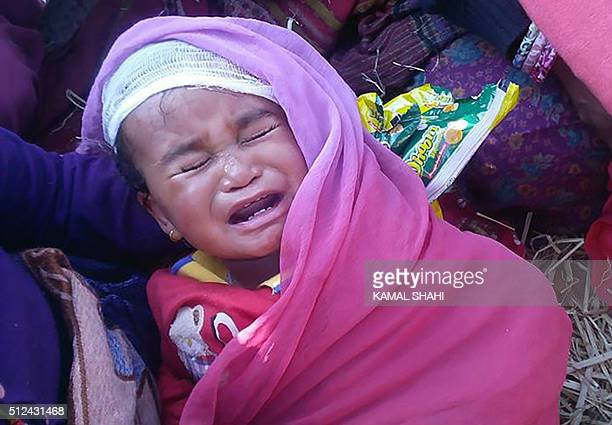 A Nepalese resident holds a baby which survived a plane crash near the wreckage of the Kasthamandap Air plane which crashed in Kalikot district some...