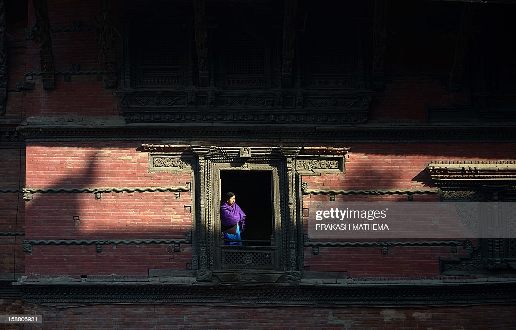 A Nepalese resident looks on from a window as member of indigenous Gurung tribe take part in a New Years celebration ceremony known as 'Tamu Lhosar ' in Kathmandu on December 30, 2012, held to celebrate their New Year or Lhosar. Gurungs number some 700,000 people about three percent of the Himalayan nation's population and are mainly concentrated in the country's central region. AFP PHOTO/Prakash MATHEMA
