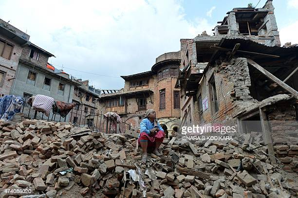 A Nepalese resident sits in the ruins of a collapsed house after an earthquake in Baktarpur on the outskirts of Kathmandu on May 20 2015 Nearly 8500...